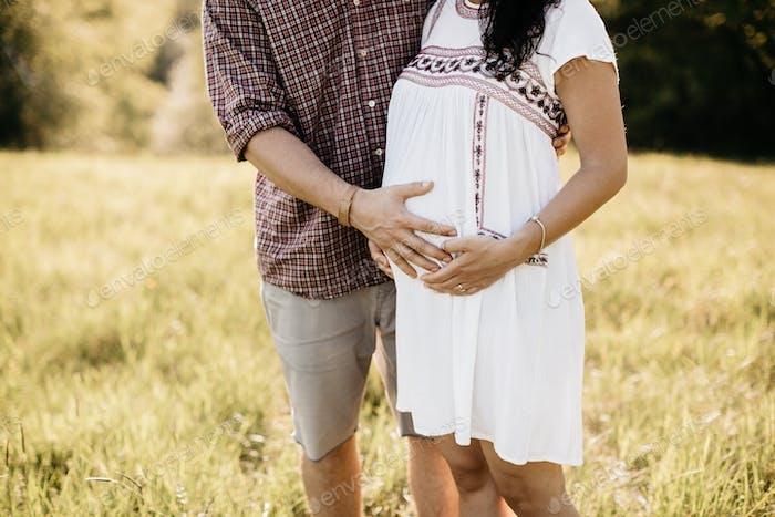 Ausgeschnittenes Bild eines erwartenden Paares umarmt