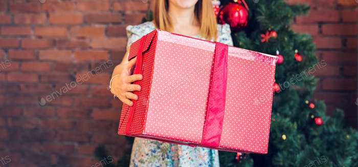 Close-up of woman with a gift box over christmas tree background