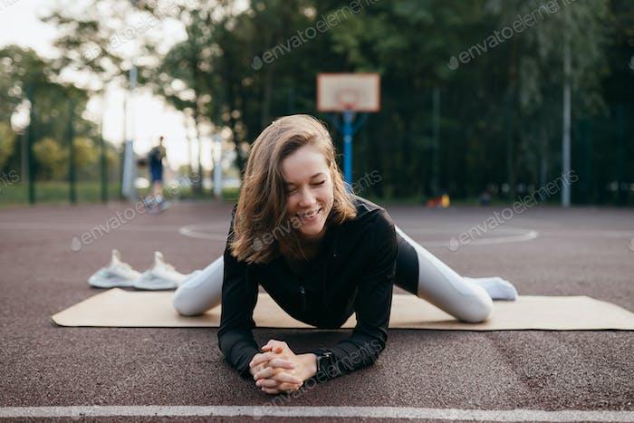 Mujer joven en forma en ropa deportiva trenes al aire libre en el patio de recreo