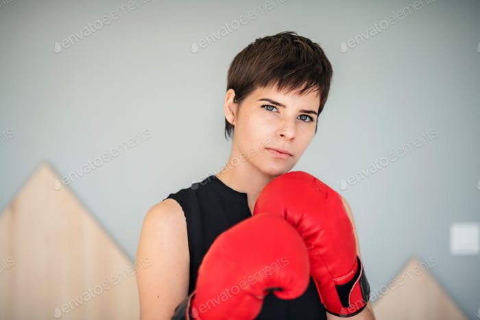 Front view of young woman with boxing gloves standing indoors at home.