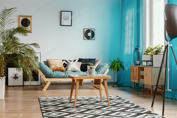 Gallery of posters on empty white wall in stylish living room in