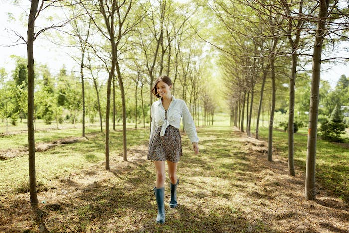 A young woman walking down an avenue of trees in woodland.