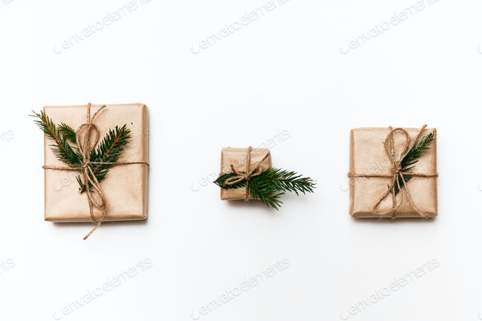 Three Vintage gift boxes with spruce branches on white isolated background, top view