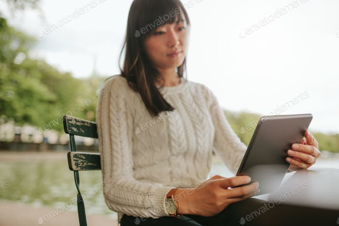 Young woman reading ebook on her digital tablet