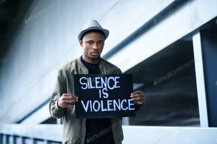 Man with silence is violence sign standing outdoors, black lives matter concept