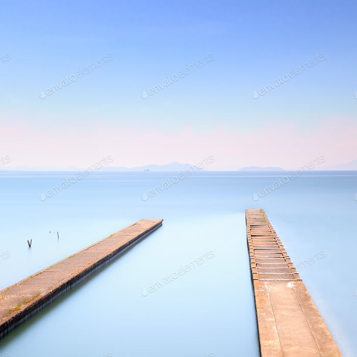 Two concrete pier or jetty on a blue sea. Hills on background