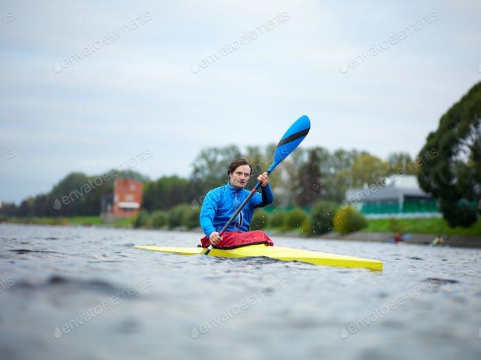 Junge konzentrierte kaukasische Sportler in Schwimmjacke Paddeln