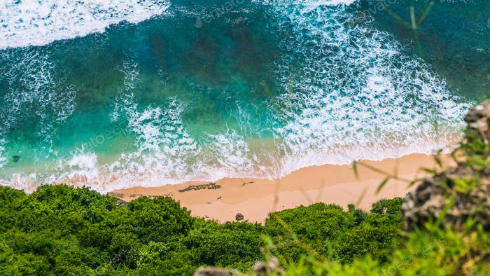 Aerial view of rolling turquoise ocean waves over pure clear sandy beach on sunny day. Surrounded by