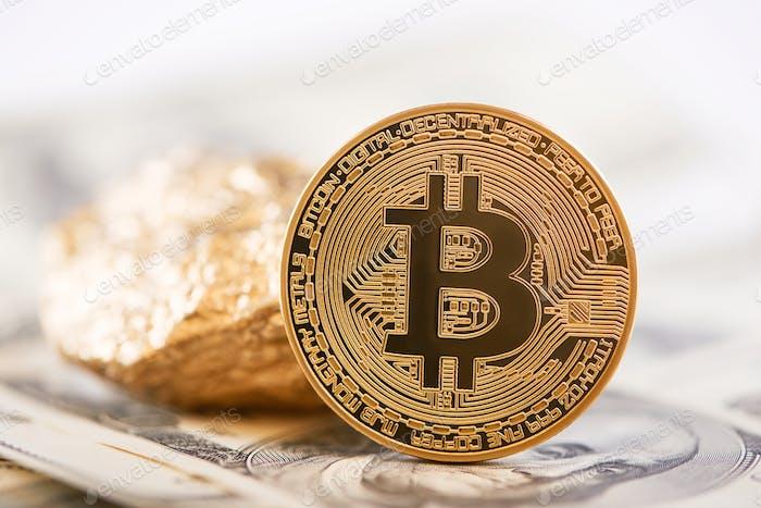 Haupt-Kryptowährung goldener Bitcoin und Goldklumpen dargestellt auf dem Hintergrund von Dollar-Banknoten
