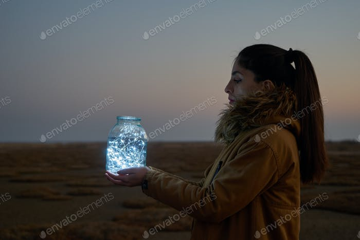 Girl is holding fairy lights in a jar on winter dry landscape