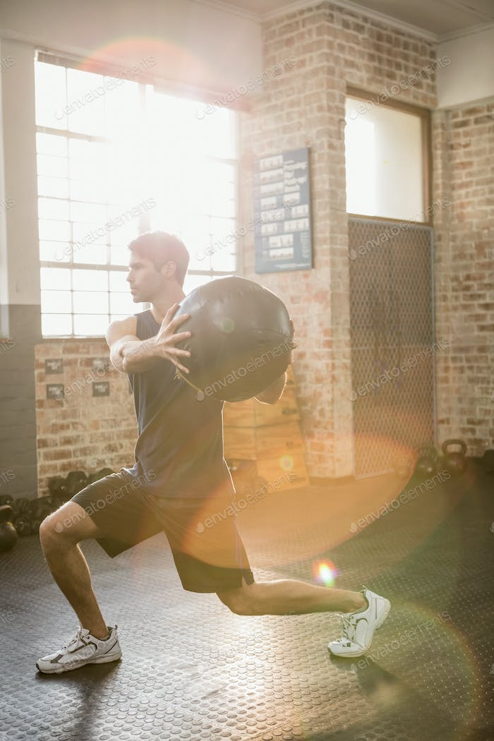 Man doing exercise with medicine ball at the gym