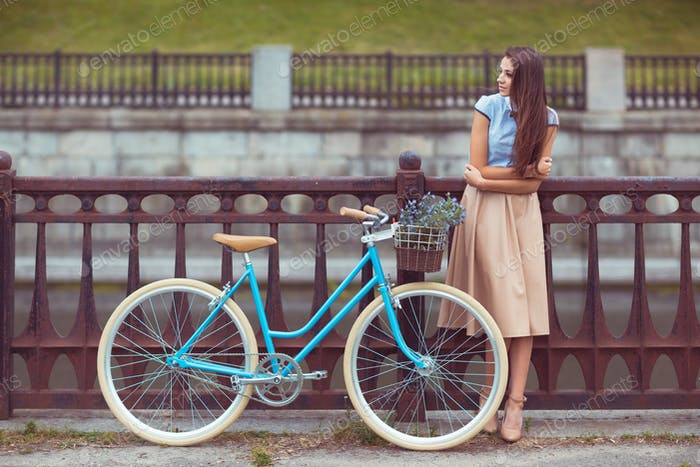Young beautiful, elegantly dressed woman with bicycle, summer an