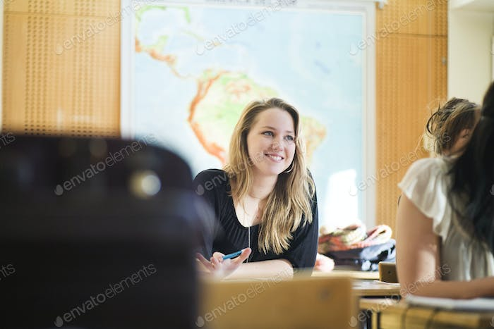 Happy high school student sitting at classroom