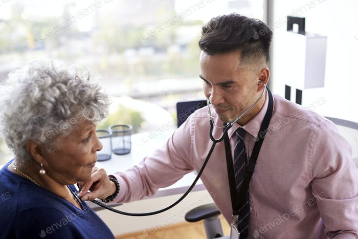 Male Doctor In Office Listening To Senior Female Patients Chest Using Stethoscope