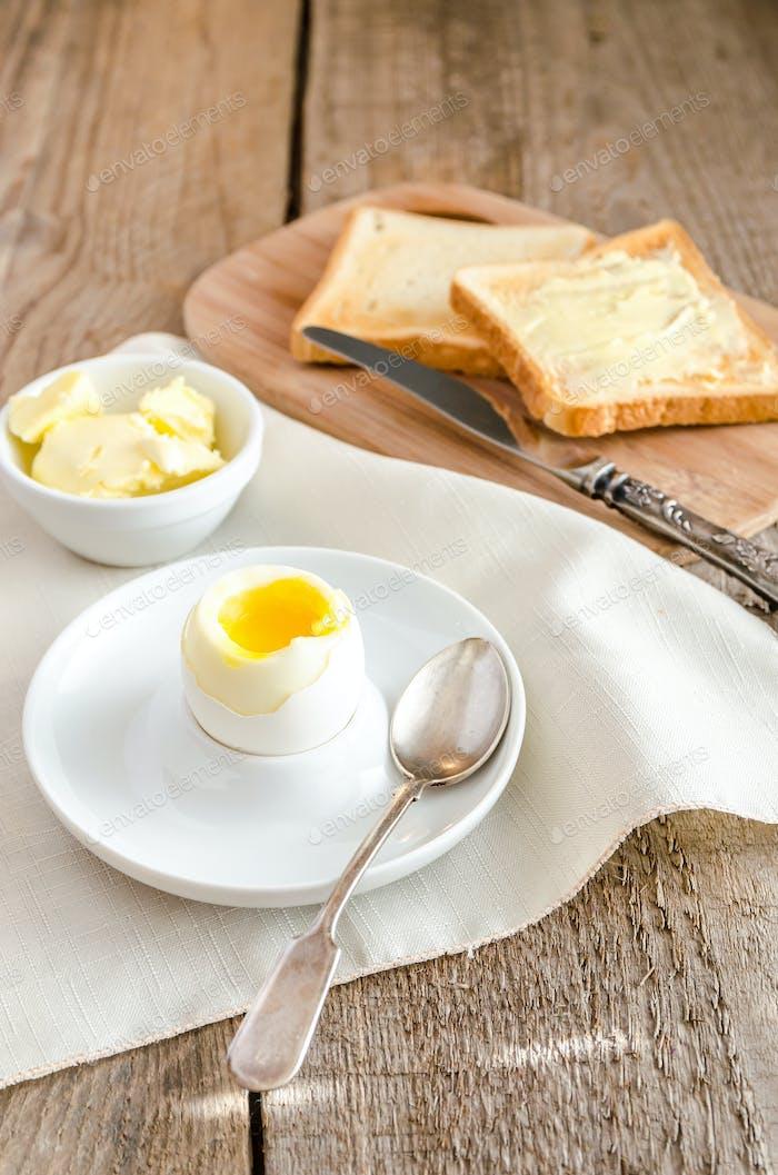 Gekochtes Ei mit knusprigen Toast auf dem Holztisch