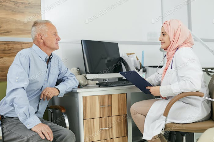 Middle-Eastern Female Doctor Consulting Senior Patient