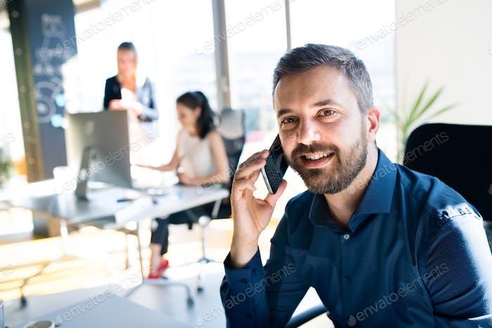 Drei Geschäftsleute im Büro arbeiten zusammen.