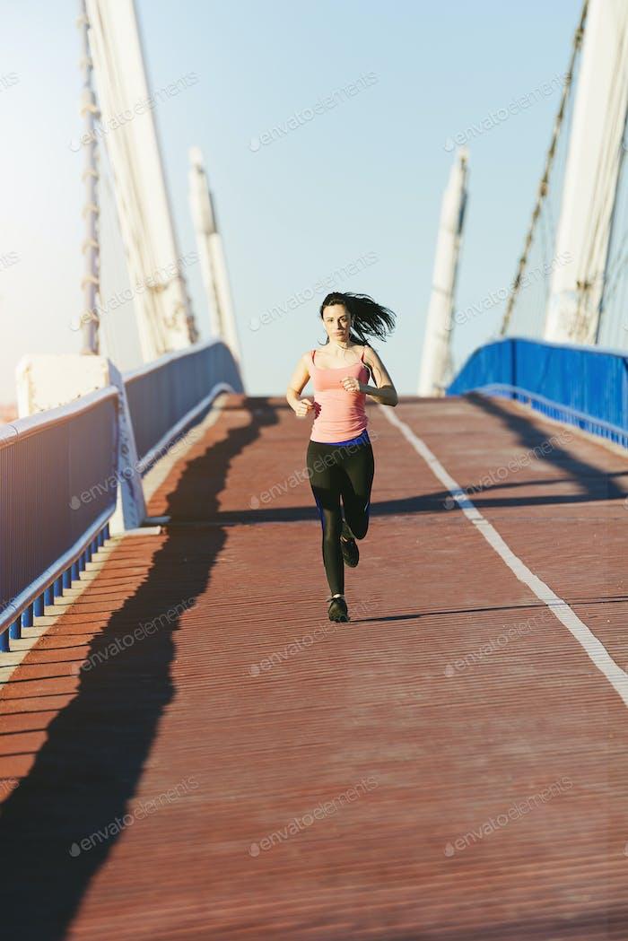 Young fitness woman runner running on city bridge.