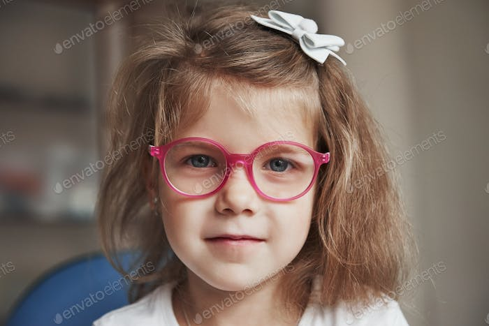 Photo of young blonde haired female child in pink glasses sitting in doctor cabinet