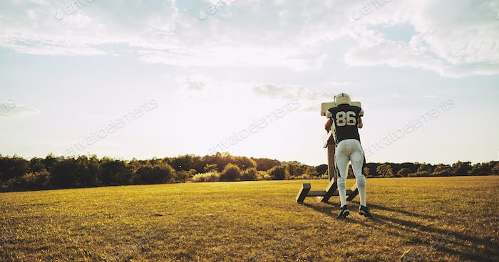 American football player doing tackling drills on a sports field