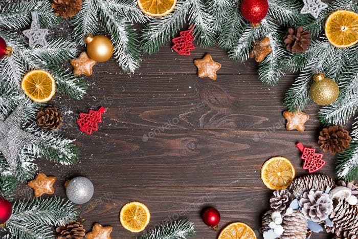 Christmas greeting card with decor and fir tree branch on a dark wooden background. Top view with