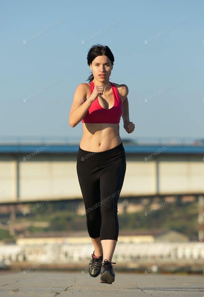 Beautiful young sports woman running outdoors