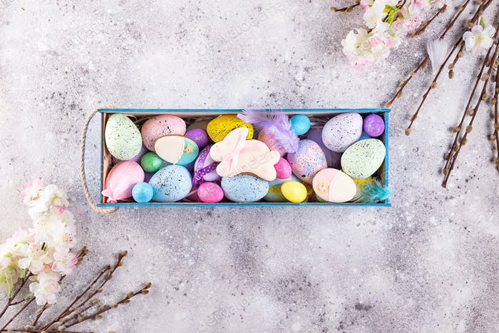 easter colorful eggs painted in bright colors and glazed cookie bunny with straw nest in wooden box