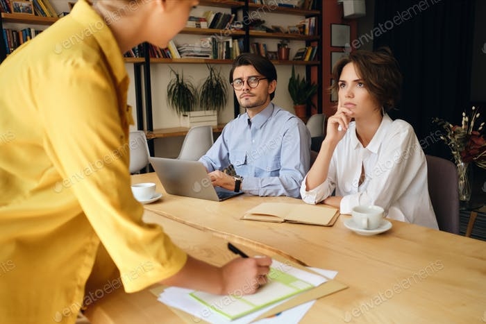 Young thoughtful business colleagues working with laptop attentively listening to boss in office