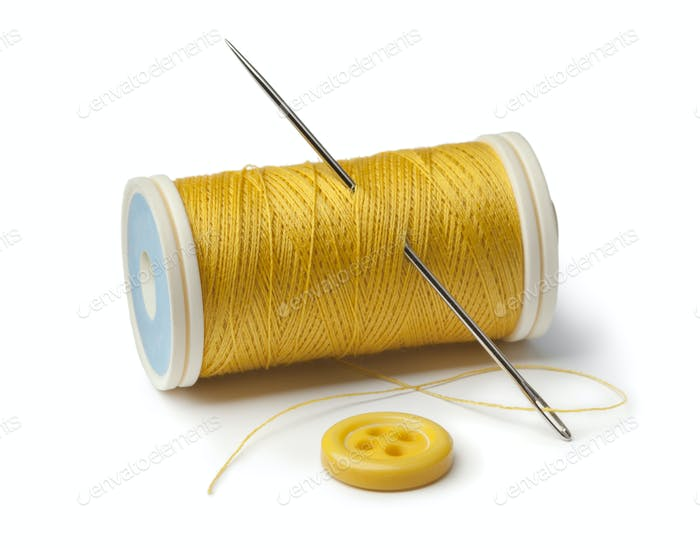 Yellow bobbin, needle and sewing button