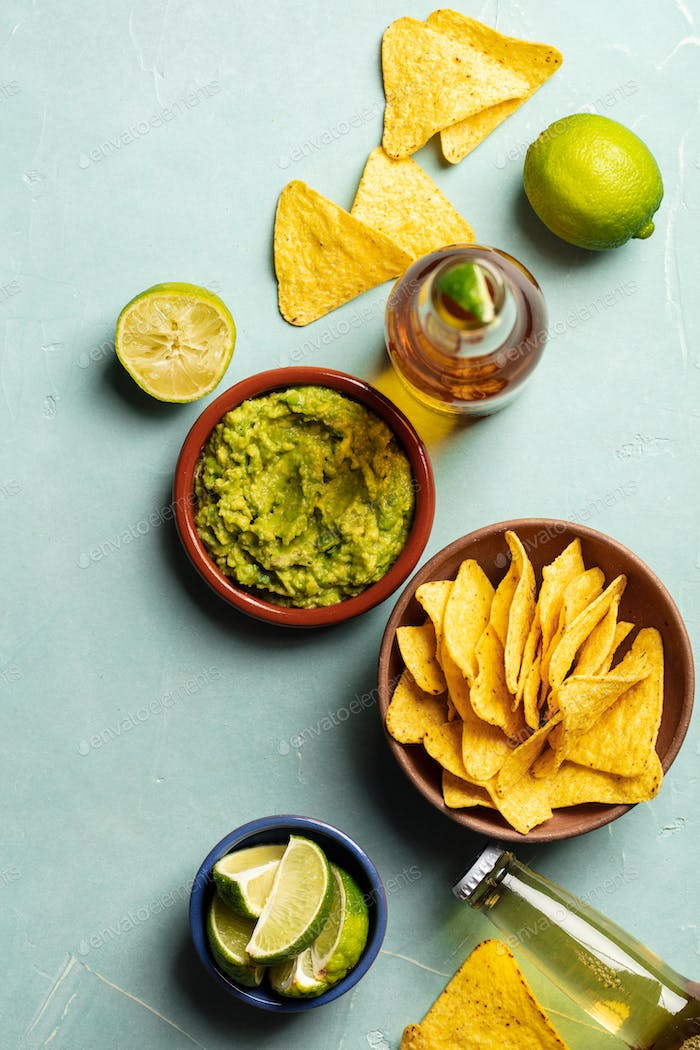 Nachos, guacamole and beer on blue background,