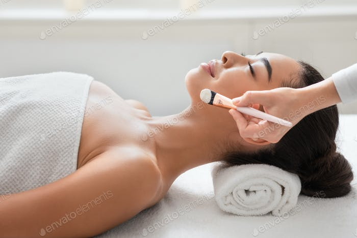 Relaxed asian woman enjoying beauty treatments in spa centre