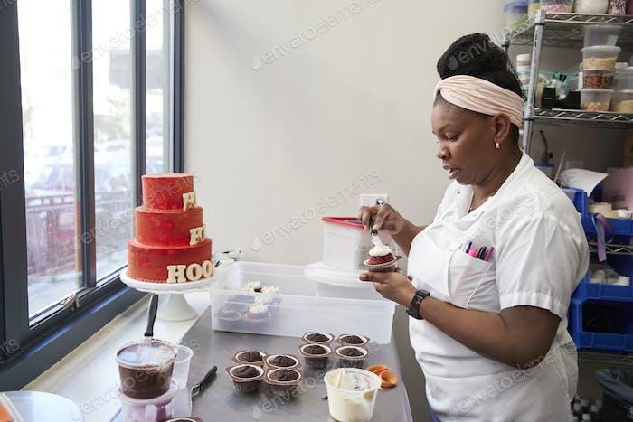 Junge schwarze Frau Zuckerguss Kuchen bei einer Bäckerei