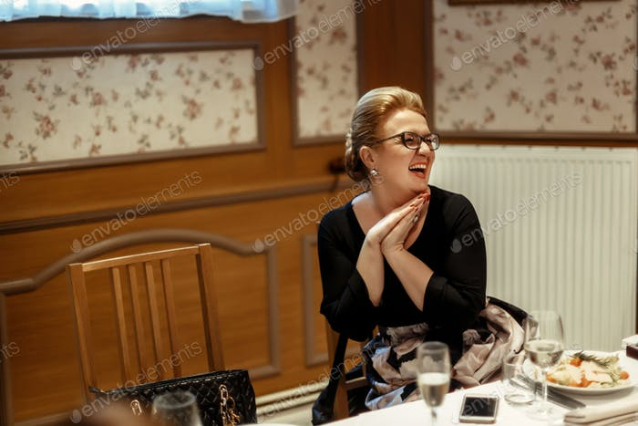 happy stylish woman in glasses laughing at celebration in restaurant