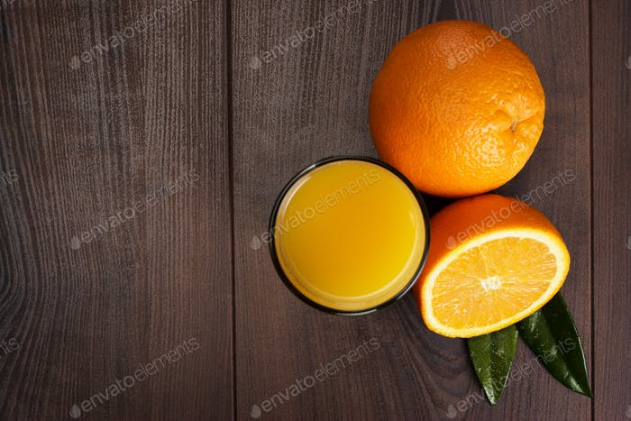 Fresh Orange And Glass With Juice On The Wooden Background