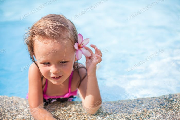 Little cute girl with flower behind her ear in the swimming pool
