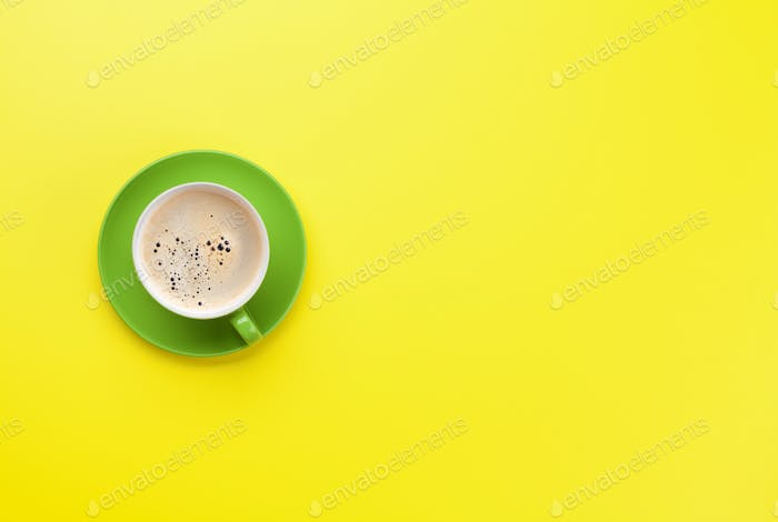 Green coffee cup over yellow background