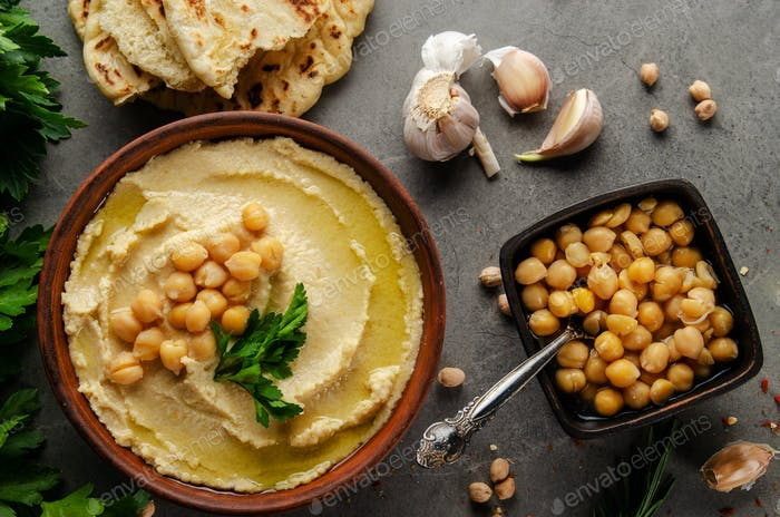 Hummus topped with chickpeas, sun dried tomatoes and green coriander leaves on stone table