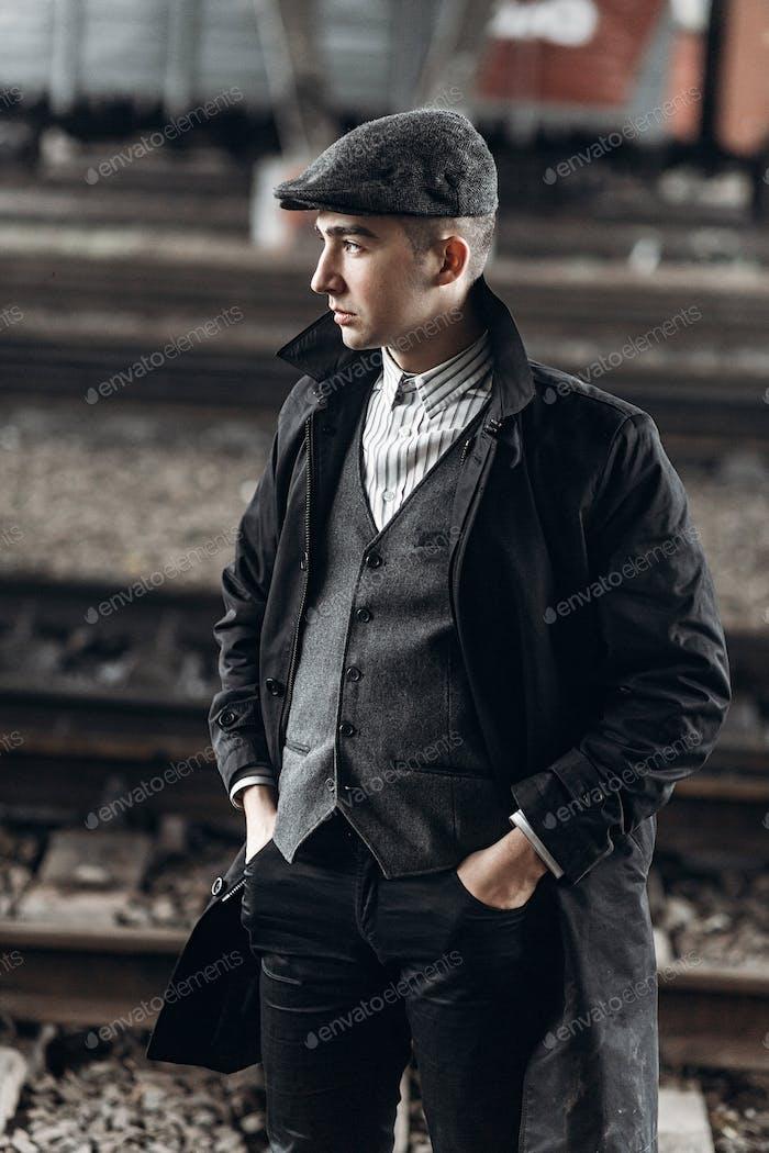 Stylish man posing on background of railway