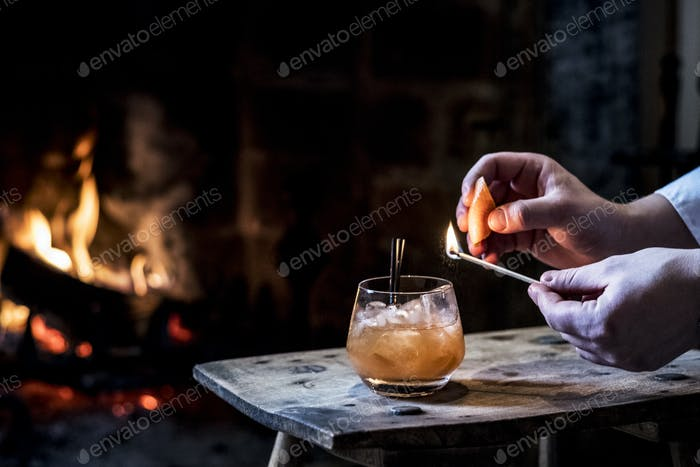 Close up of human hand striking match over glass with alcoholic drink.
