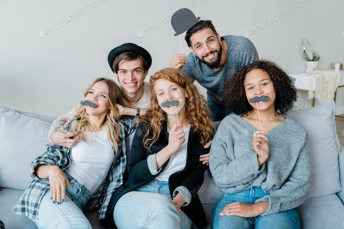 Three funny girls with moustaches sitting on couch with two happy guys behind