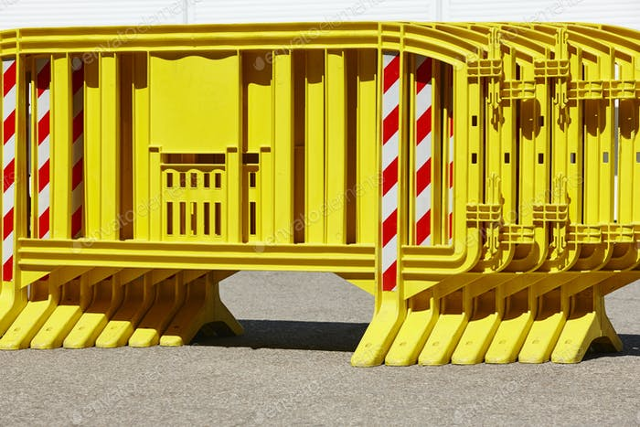 Yellow plastic barrier fence over an asphalt road. Security