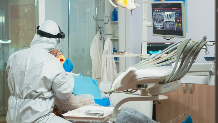 Dental technician in protective equipment lighting the lamp