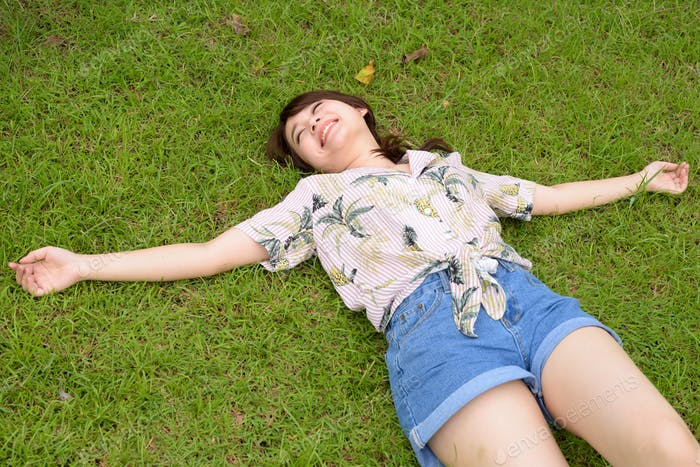 Young beautiful Asian tourist woman relaxing at the park