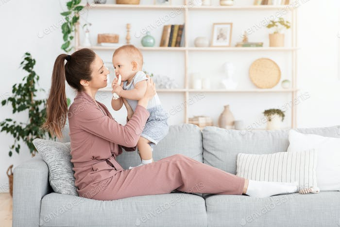 Mother-baby emotional attachment. Young Mom bonding with adorable toddler baby at home