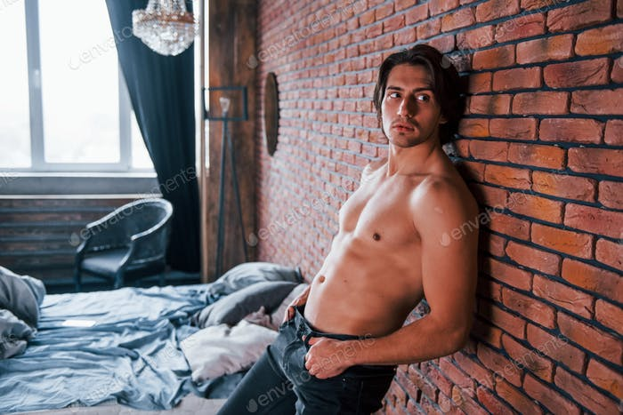 Shirtless sexy man leaning on the brick wall in bedroom at morning time