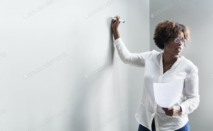 Black woman writing on a whiteboard