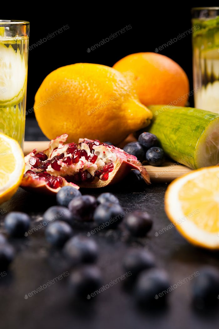 Berried, pomegranate and lemons on dark wooden background