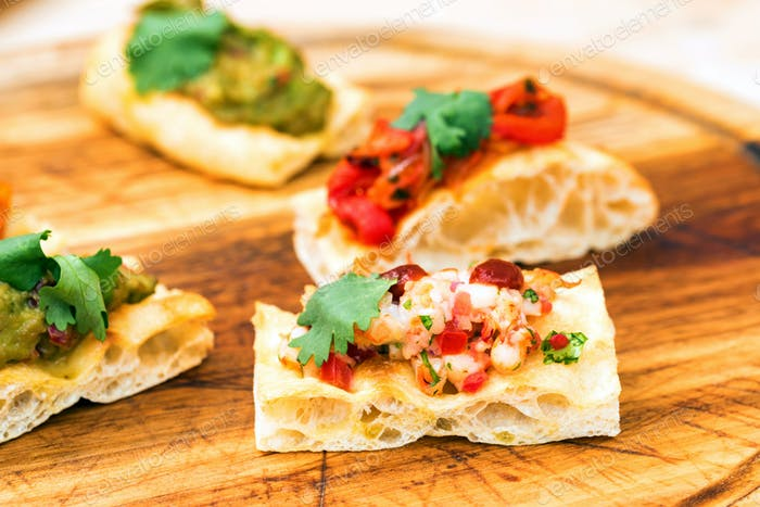 Prawn bruschetta with vegetables on wooden board close up