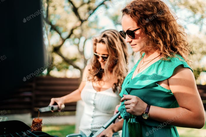 Two woman cooking at barbecue party, having drinks and smiling