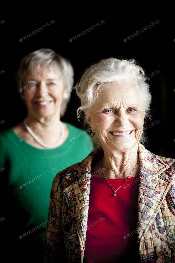 Portrait of smiling senior woman with friend against black background